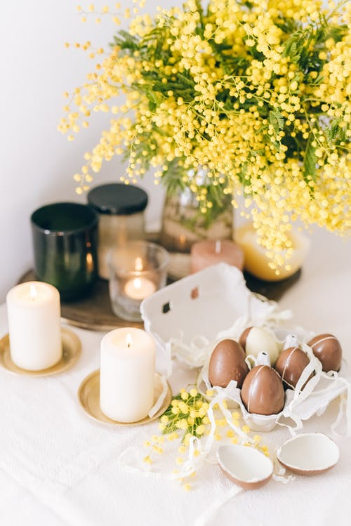 Colored Eggs And Burning Candles On Table