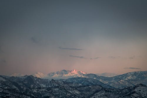 From above spectacular landscape of rough rocky mountain range covered with snow in sunlight at sunset time with cloudy sky