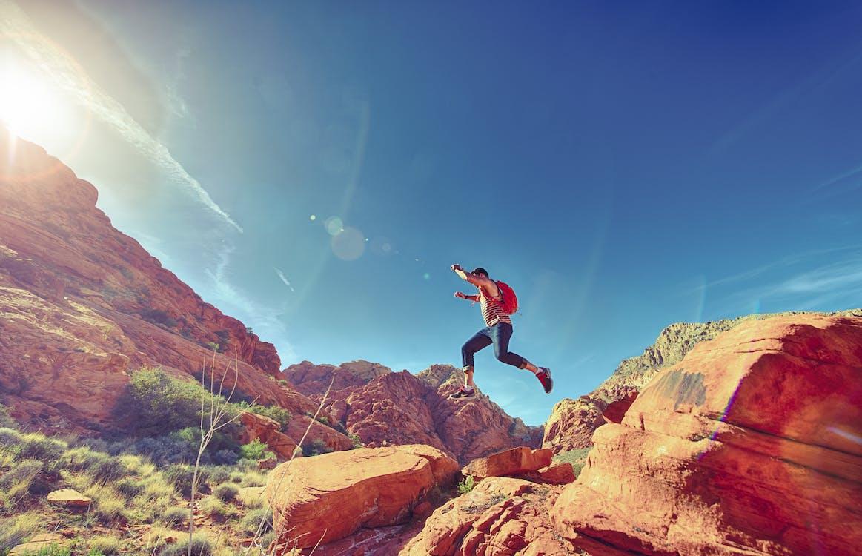 Man Jumping on Rock Formation Under Blue Sky