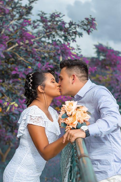 Romantic ethnic newlyweds kissing in garden