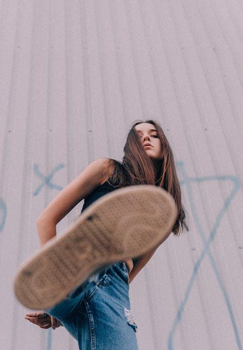 Provocative female millennial kicking on camera