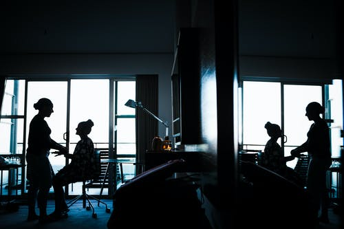 Side view silhouettes of anonymous female friends looking at each other while communicating in modern apartment