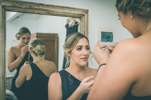 Elegant young bridesmaids preparing for wedding celebration