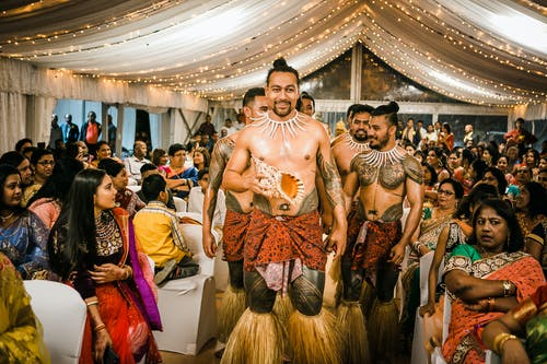 Young shirtless Samoan male dancers in traditional outfits standing amidst Indian guests in decorated canopy tent during wedding party