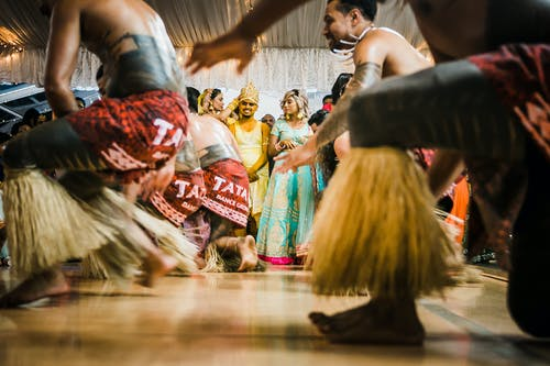Happy Indian newlyweds with guests enjoying dance show during wedding party