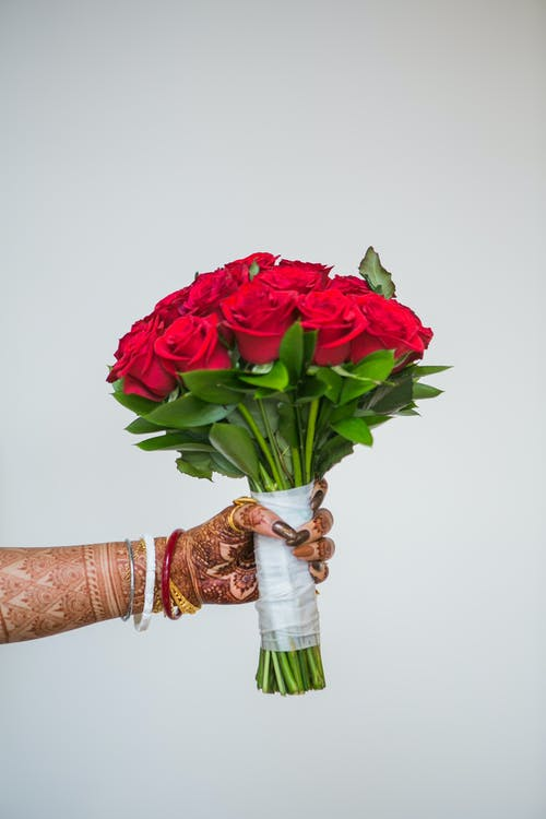 Woman with mehendi and bouquet of fresh red roses
