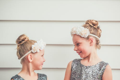 Cheerful little adorable sisters in silver dresses and white headbands smiling and looking at each other