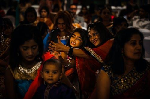 Positive Indian women in festive wear on ceremony