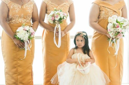 Ethnic girl standing near crop women during wedding ceremony
