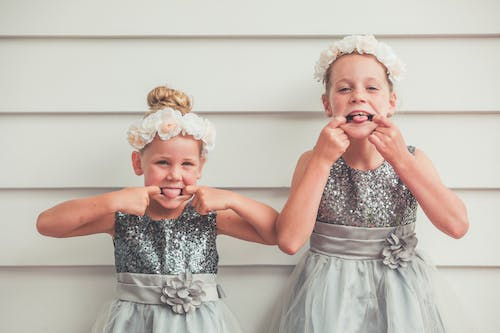 Happy sisters in stylish clothes and floral headbands making faces and looking at camera while standing near wall during festive event