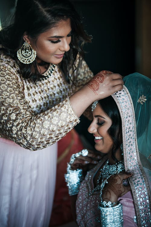 Woman helping Indian bride to get ready for wedding