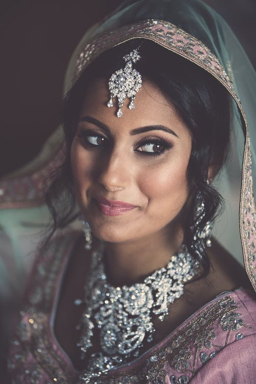 Positive Indian bride with black hair wearing traditional veil and garment looking away while sitting in room during wedding celebration
