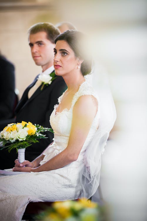 Serious bride with flowers and groom during wedding ceremony