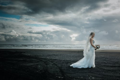 Peaceful bride with flowers standing on beach