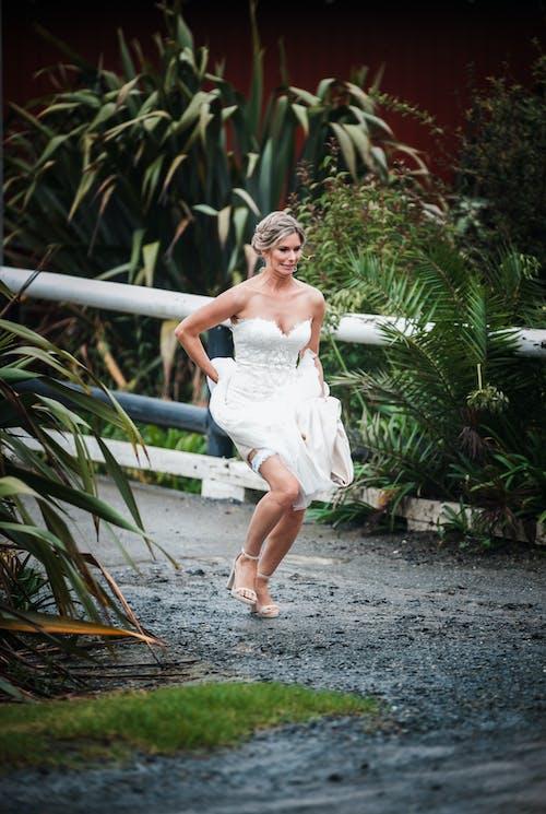 Stylish bride running on walkway near green plants