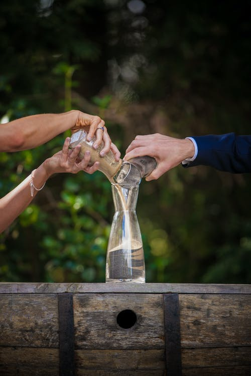 Unrecognizable groom and bride pouring sand from jars into glass vase while performing wedding ritual on street during holiday celebration on blurred background