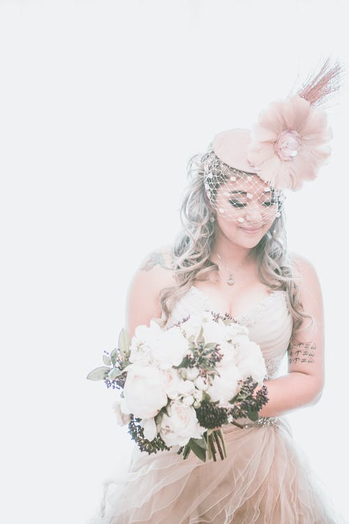 Bride in wedding dress and headdress with bouquet of flowers