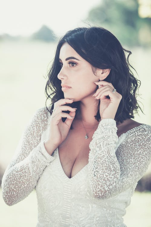 Pensive female in white dress looking away against blurred nature in daytime