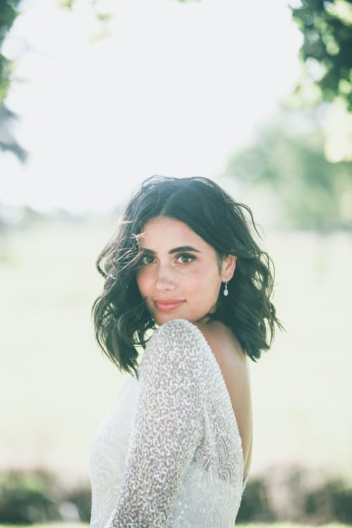 Calm woman with dark hair in elegant stylish white dress standing among green plants in nature and looking at camera in daytime