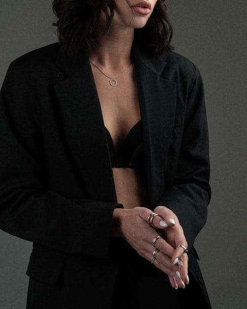 Crop unrecognizable female wearing black classy blazer on underwear with silver rings and necklace against gray background