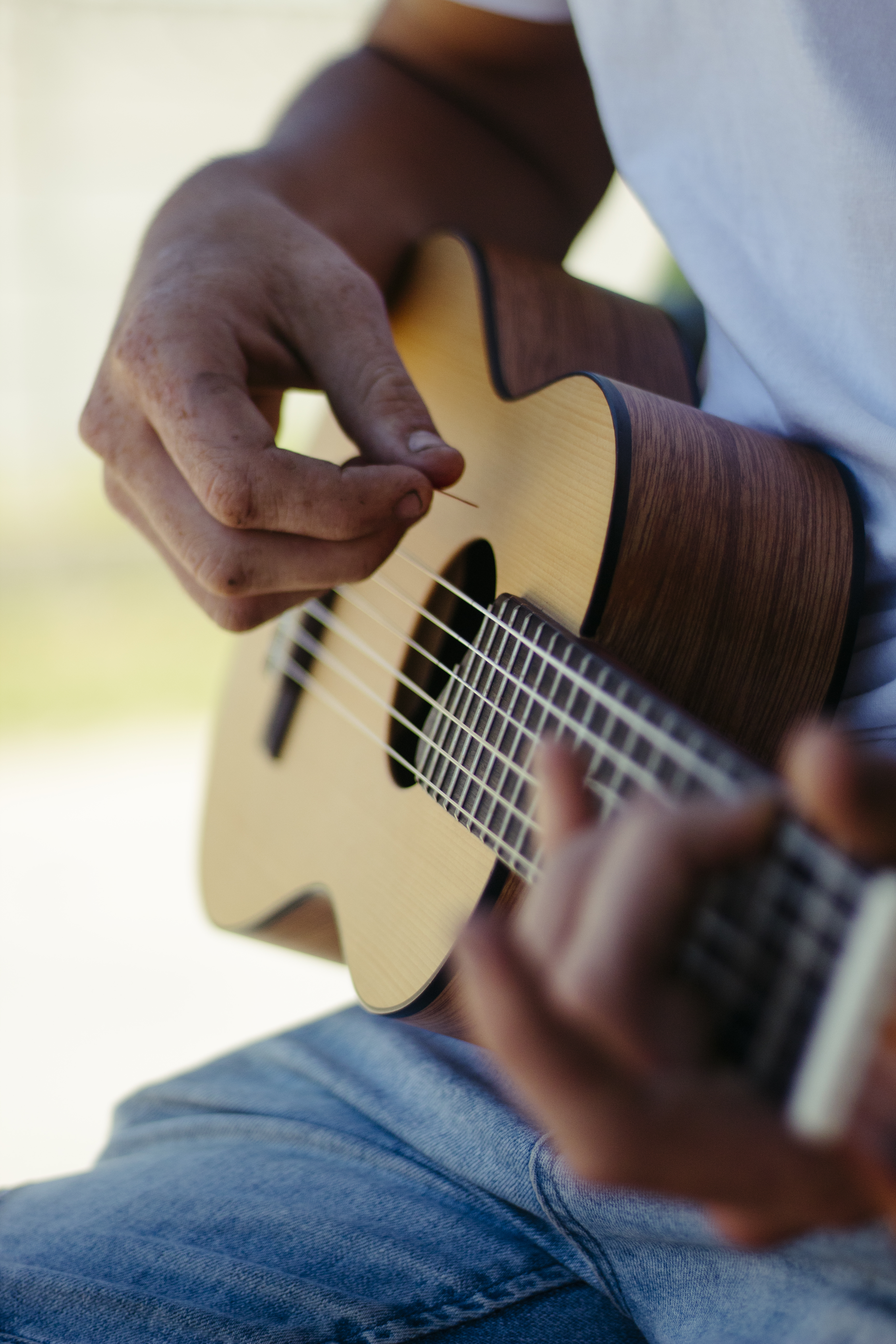 male musician playing guitar in nature