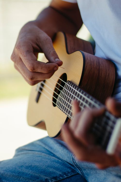 Crop anonymous male guitarist pinching chord on fretboard while spending free time in nature