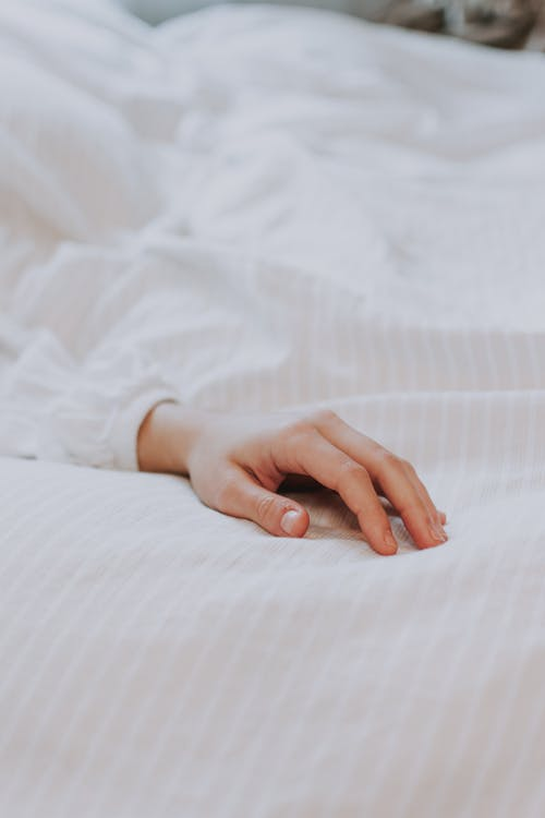 Crop hand of unrecognizable person in white shirt lying on comfortable soft bed in morning