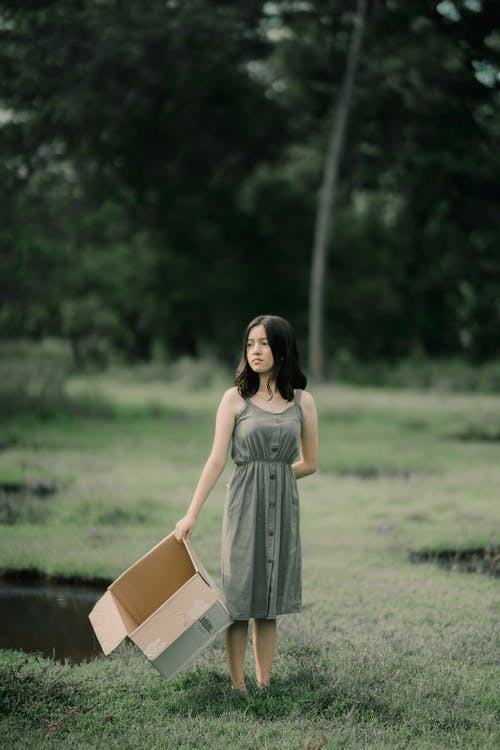 Dreamy woman with cardboard box on meadow in park