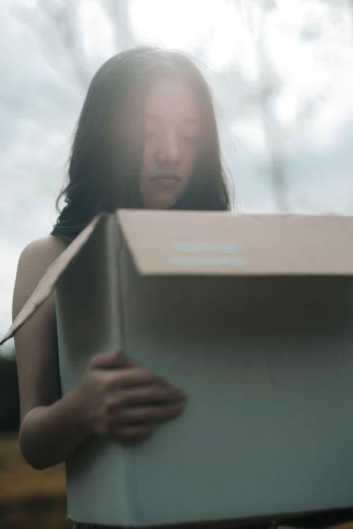 Young dreamy female with black hair and closed eyes carrying carton box in sunlight