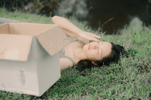 Side view of young gentle female touching face on lawn between cardboard box and pond