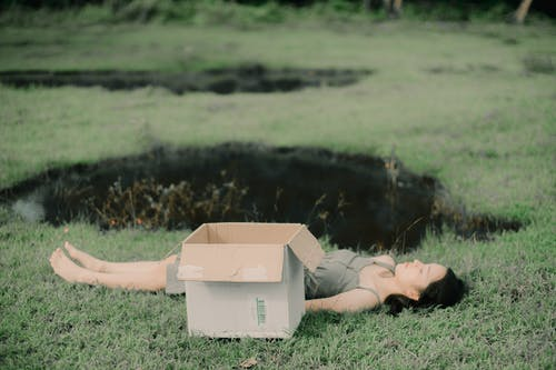 Barefoot woman napping between carton box and pond on lawn