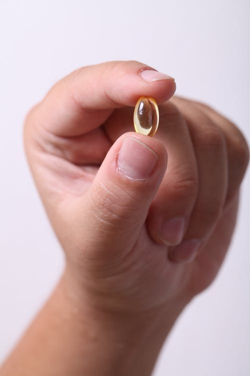 Person Holding Oval Clear Capsule