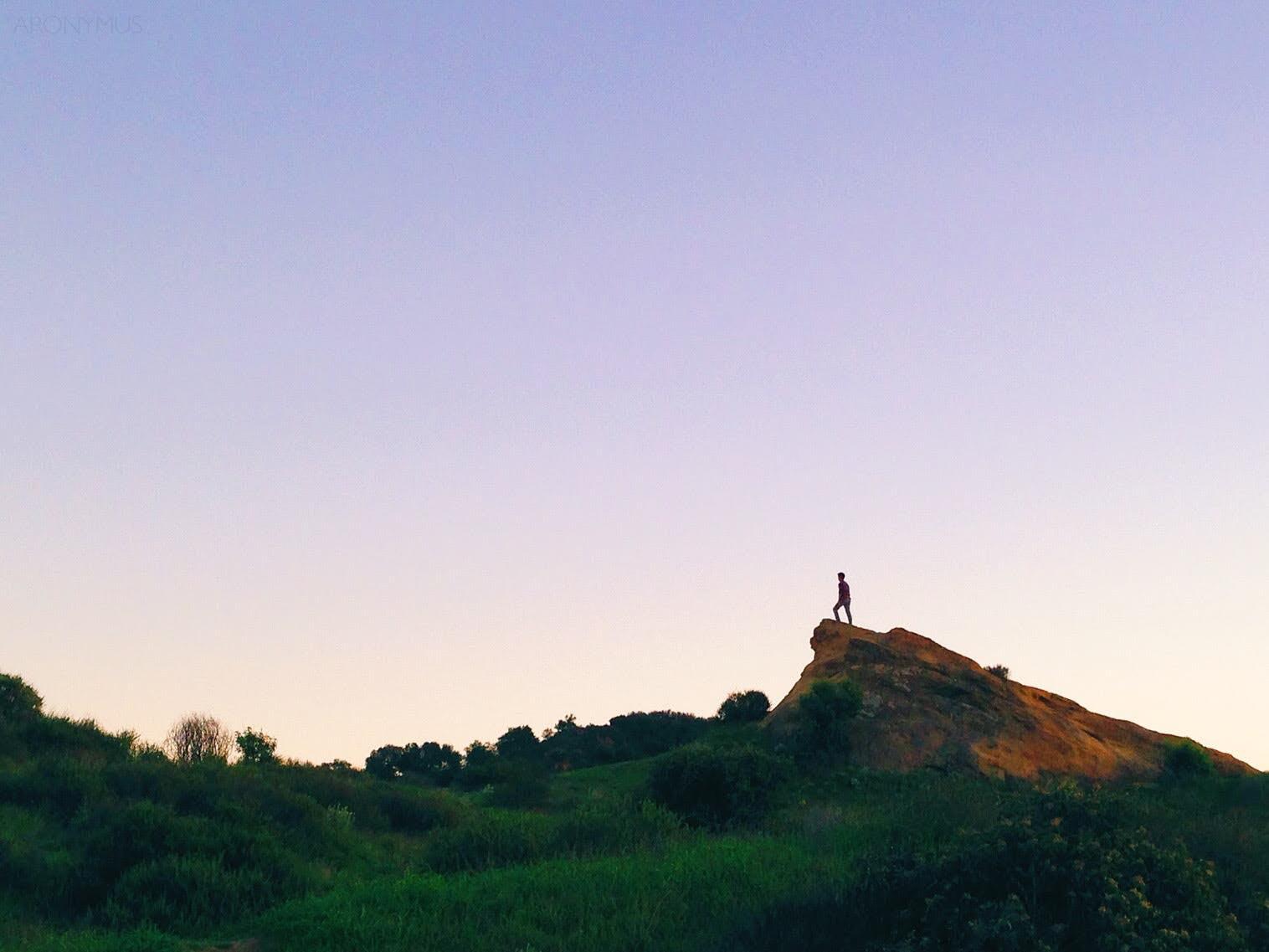 Person on a Brown Rocks Near Green Grass Under Blue Sky Under Daytime