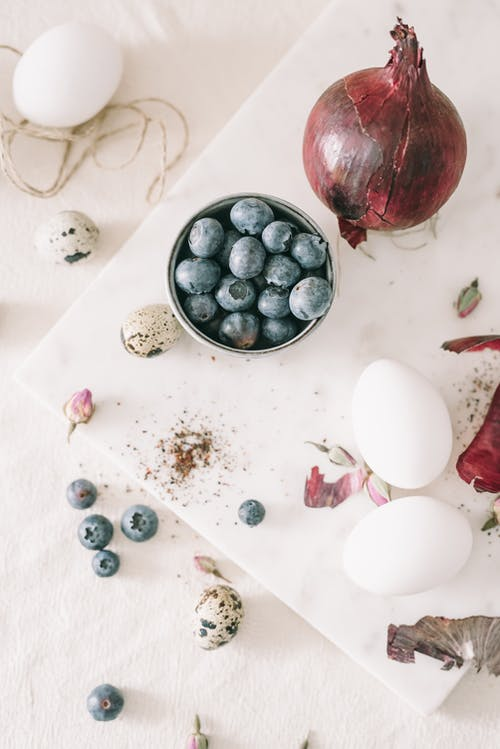 Bowl Of Blueberries Beside Eggs And Red Onion On Table