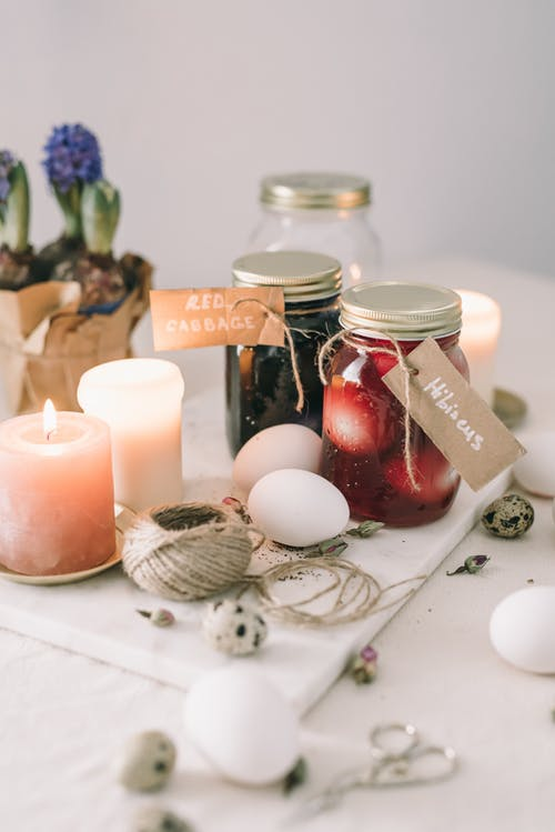 Eggs Inside Glass Jars With Black And Red Liquid