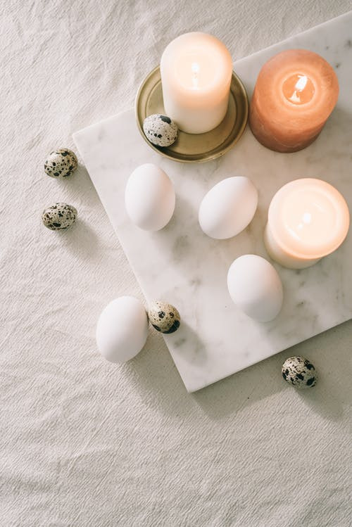 Lighted Candles And Eggs On Marble Surface