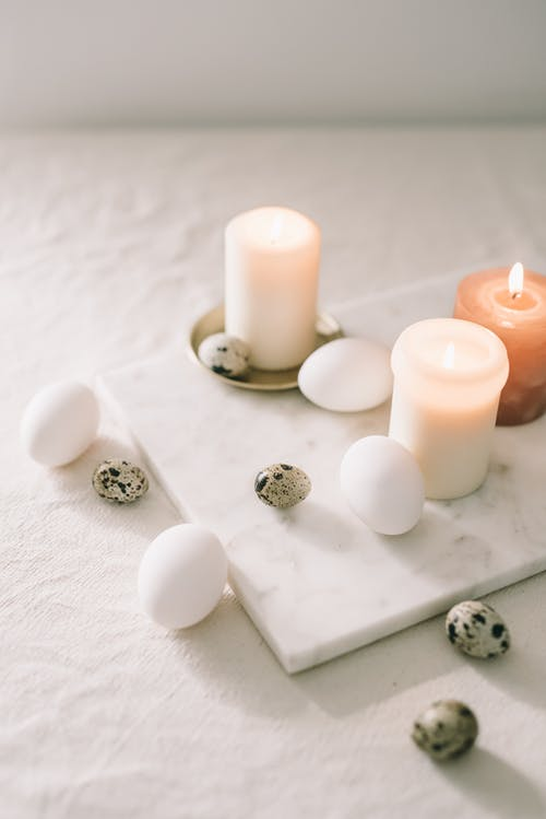 Eggs And Lighted Candles On Marble Top