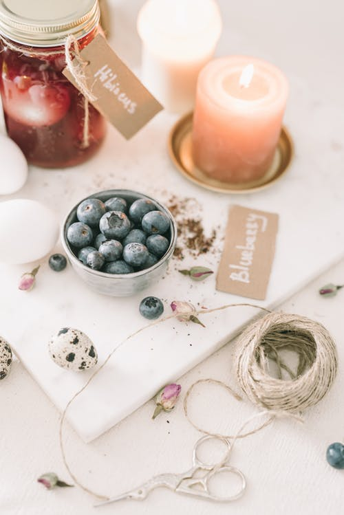 Blueberries On A Bowl Beside A Lighted Candle