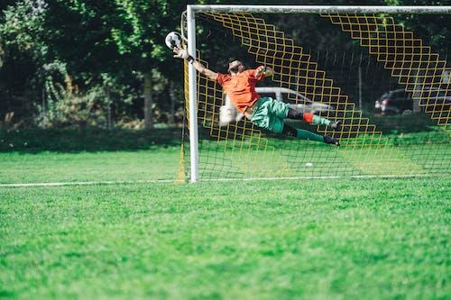 Man in Orange Shirt Playing Soccer on Green Grass Field