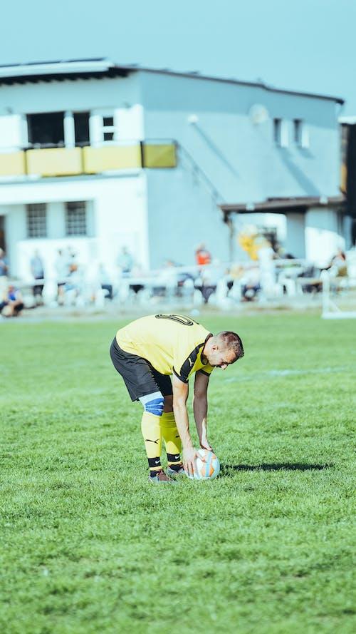 Man in Yellow Soccer Jersey Kicking Soccer Ball on Green Grass Field