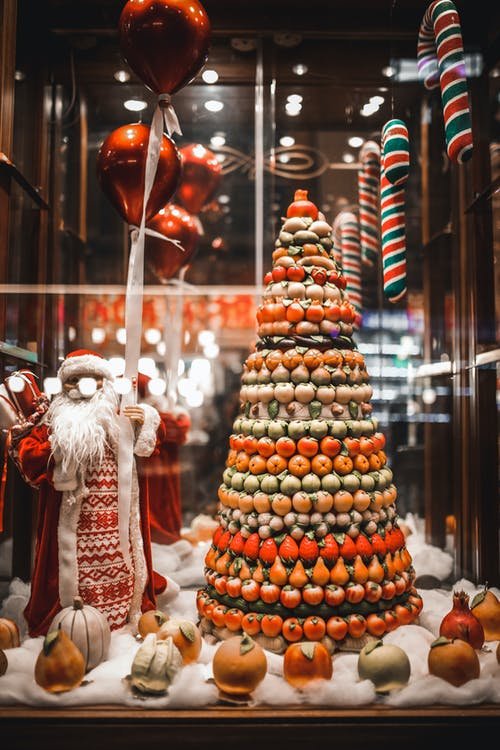 Showcase of triangle shaped sweets stand and Santa figurine placed on artificial snow and decorated with festive baubles