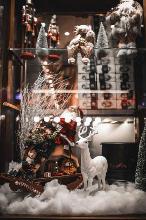 Festive decorations with cute Santa Claus and deer figurines arranged on artificial snow in showcase