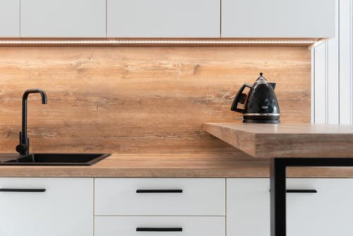 Kettle placed on wooden counter of minimalist kitchen