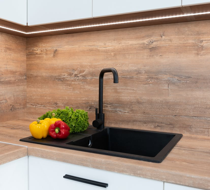Fresh green lettuce with red and yellow bell peppers placed near sink on wooden tabletop in modern kitchen