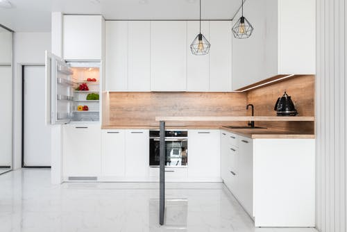 Interior of contemporary light kitchen with white furniture and modern appliances