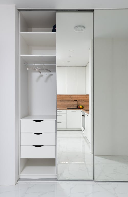 Wardrobe in hallway with mirrored wall reflecting furniture of modern kitchen in light apartment