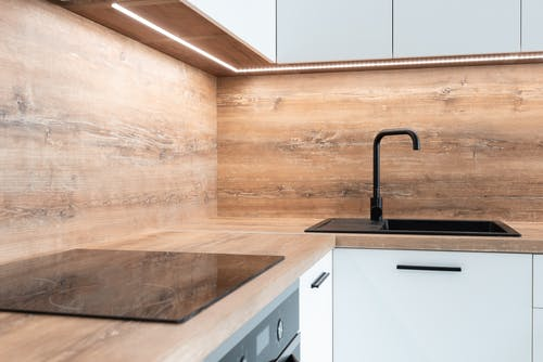 Modern black appliance and sink with faucet in stylish kitchen with wooden walls and white furniture