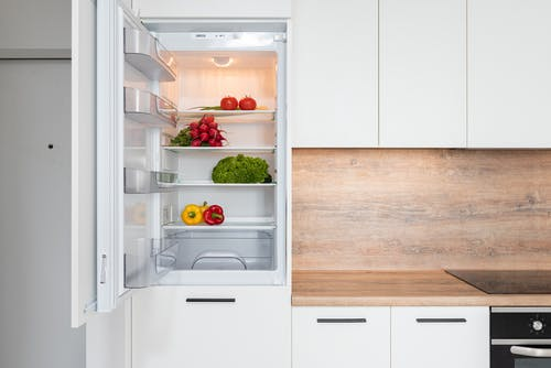Fridge with different vegetable in modern kitchen