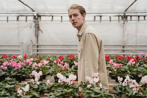Man in Brown Coat Standing Near Pink Flowers