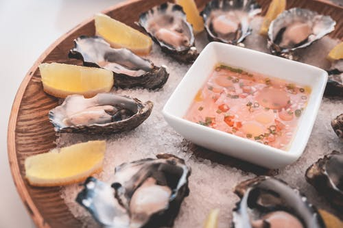 Delicious oysters with lemons and sauce served on ice